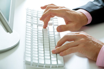 Image of male hands pushing buttons of keyboard