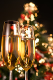Blurred christmas tree and two champagne glasses