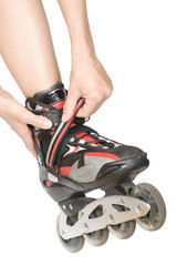 woman putting on rollerblades, on white background