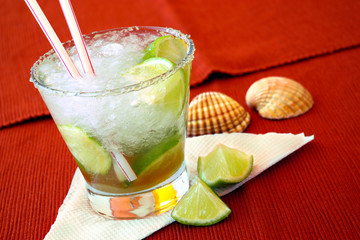Brazilian caipirinha cocktail with limes and sea-shells