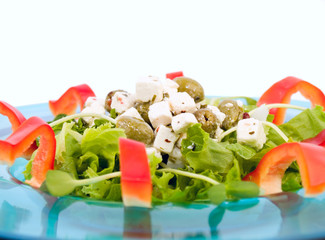 Salad with feta cheese and olives on a teal glass plate
