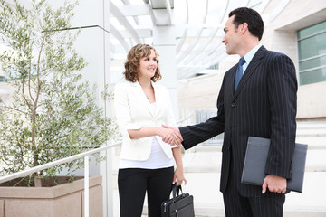 Attractive man and woman business team shaking hands
