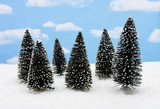 A group of evergreen trees on snow with sky background poster