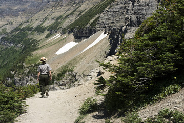 a park ranger walking on Highline Trail in Glacier National Park