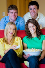 Four young people eating popcorn at home on the sofa