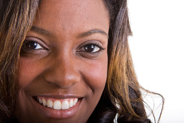A closeup of a young black woman with a dazzling smile