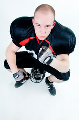 American football player sitting on his helmet