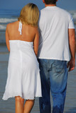 young couple having romantic stroll on the beach poster