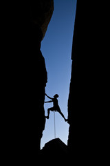 Rock climber silhouetted as he climbs up a chimney .