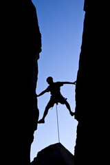 Rock climber silhouetted as he climbs up a chimney.