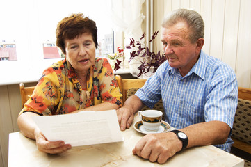 Senior couple studying document together in home