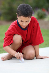 Boy in his driveway playing with chalk
