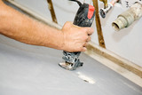 Contractor using a rotary saw to cut holes in drywall poster