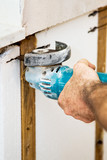 Closeup of electrician cutting through insulation with grinder. poster