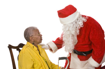 Pleasant man in a santa suit talking to an elderly lady
