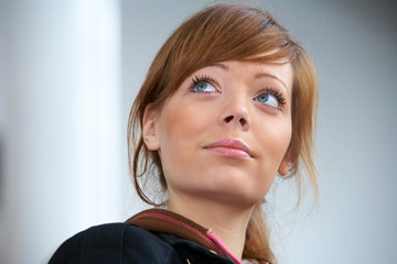 Teenage girl in modern building, looking up