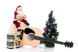 Christmastree with Santa Claus sitting on guitar with present