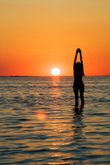 Silhouette of the young woman with hands upwards on a sunset