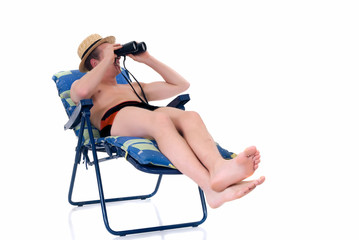 Young man in deck chair looking trough magnifying glass,