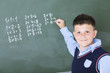 A boy does multiplication on chalkboard