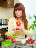 Beautiful woman in kitchen cooking meal poster