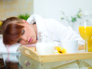 Beautiful woman in kitchen sleeping on table