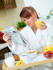 Beautiful woman in kitchen eating tasty breakfast