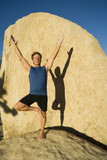 A man practices yoga on the boulders in Joshua Tree. poster