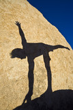 A man practices yoga on the boulders. poster