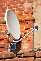 Satellite receiver dish on the old brick wall
