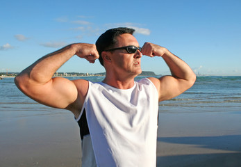 Man doing stretching and flexing exercises on the beach