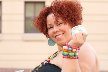 Plus size female model with red curly hair, holding money
