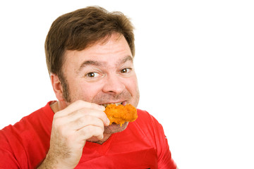 Middle aged man in football jersey enjoying a buffalo wing.