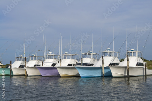 Row of multi-colored nice deep sea fishing boats in a marina.