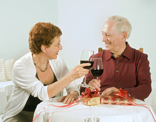 senior couple having wine and exchanging gifts