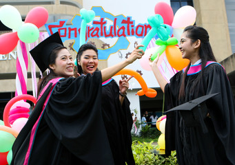 Beautiful Asian university graduates celebrate their success.