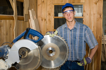 The carpenter holds a circular saw blade in a hand.