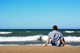 Man sitting on lakeshore and  looking on waves. poster