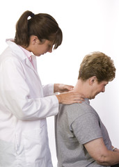 physical therapist checks a patient's spine in the neck