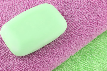 an abstract of green and purples towels with soap on top
