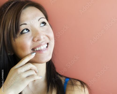 Adorable young woman smiling and looking towards copy space area