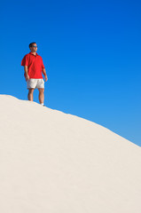 Man looking off into the distance on top of a white sand dune