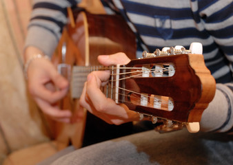 Detail of hands playing a guitar.