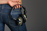 Against female back in jeans the hand holds ear-phones poster