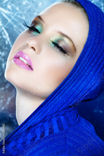 beautiful woman with long feather eyelashes in blue top