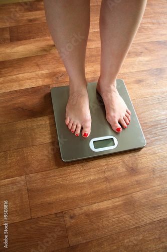 A woman standing on scales on a wooden bathroom floor