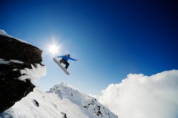 Snowboarder jumping through air after rock drop