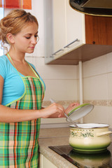 Woman prepares soup on kitchen