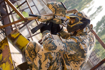 Paintball player in camouflage uniform outdoors