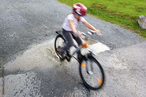 Leinwandbild Motiv bicycling through puddle